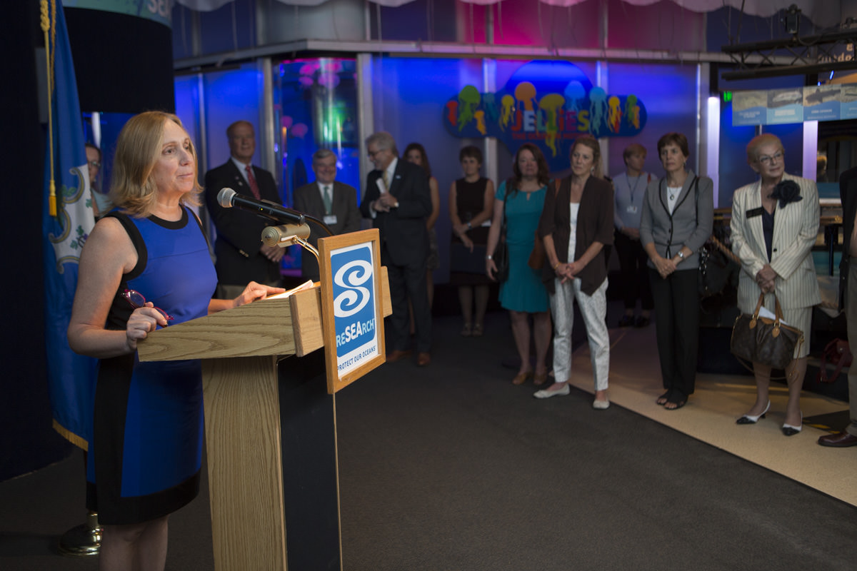 Diane Weaver Dunne takes the podium at the launch of CRISAccess at Mystic Aquarium.
